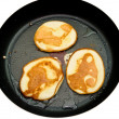 Fritters on a frying pan pancakes on the griddle on the white isolated back — Stock Photo #5134726