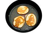 Fritters on a frying pan pancakes on the griddle on the white isolated back — Stock Photo