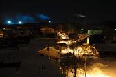 Night Village with smoking chimneys on the horizon — Stock Photo