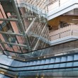 Foto Stock: Glass elevator shafts, escalators and stairs in modern office building
