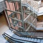 poços de elevador de vidro e escadas rolantes em um edifício de escritório moderno — Foto Stock