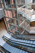 Glass lift shafts and escalators in a modern office building — Stock Photo