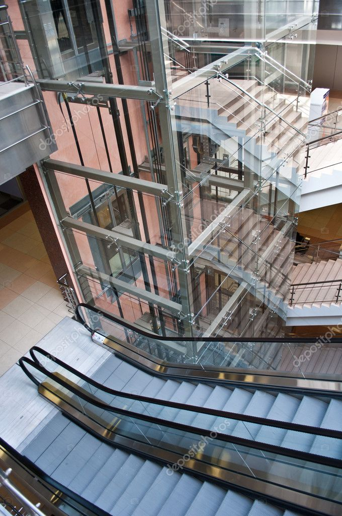 Glass lift shafts and escalators in a modern office building — Stock Photo #5311402