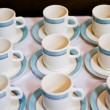 Nine white porcelain tea cups and saucers and napkins — Stock Photo