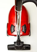 The red vacuum cleaner with a black hose on a white background — Stock Photo