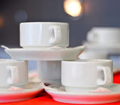Three white porcelain tea cups and saucers and napkins close up — Stock Photo