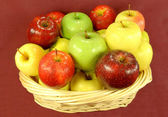 Assorted Apples in basket on red background. — Stock Photo