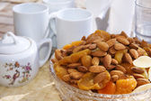 Nuts and dried fruits with a tea set — Stock Photo