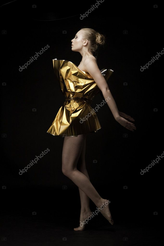 Attractive dancer in gift wrapping standing over black background.  Stock Photo #4756479