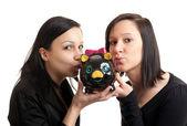 Two young women piggy bank kissing — Stock Photo