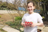 The girl holds a tray with a ripe strawberry — Stock Photo