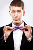 Young man in tuxedo fixing bow tie — Stock Photo