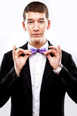 Young man in tuxedo with singlasses fixing bow tie — Stock Photo