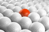 White Golf balls & one orange in the middle — Stock Photo