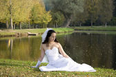 A bride sitting next to the pond — Stock Photo