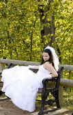 A bride sitting on a bench looking at you — Stock Photo