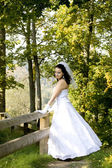 Bride next to a wooden fence — Stock Photo