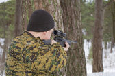 Hunter takes aim from behind a tree — Stock Photo
