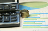 Pen and calculator on the financial table — Stock Photo