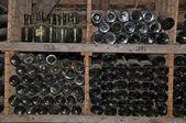 Old bottles in storage shelves — Stock Photo