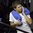 Tired young man sitting with blue towel in the fitness club — Stock Photo