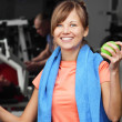 Stock Photo: Womwith apple in fitness club
