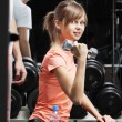 Young woman with dumbbell in fitness club — Stock Photo