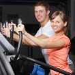 Young couple on exercise a bicycle in fitness club — Stock Photo