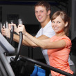 Young couple on exercise a bicycle in fitness club — Stock Photo #4829434
