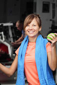 Woman with apple in fitness club — Stock Photo