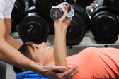 A girl's trainer shows her the correct form of exercise with dumbbell — Stockfoto
