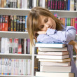 Young beautiful woman sleeping with books in the library — Stock Photo