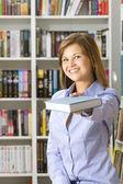 Jovem estende-se o livro na biblioteca — Foto Stock