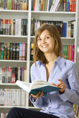 Young woman reading book in the library — Stock Photo