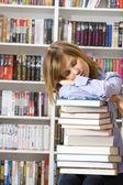 Mladá krásná žena spí s knih v knihovně — Stock fotografie