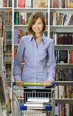Young woman shops in a bookshop — Stock Photo