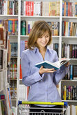 Woman shops in a bookshop — Stock Photo