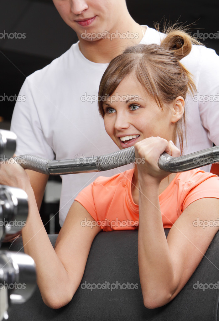 Young beautifull girl and her trainer in fitness club — Stock Photo #4928632