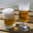 Mug and bocal of  beer on the wooden pier — Stock Photo