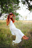 The red-haired girl in a white dress shakes on a swing in a grove — Stock Photo