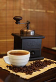 Coffee grinder, white cup of coffee and grains of fried coffee on a mat, Sh — Stock Photo