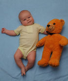 The baby and a teddy bear — Stock Photo