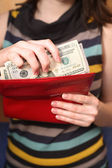 The girl gets dollars from a purse — Stock Photo
