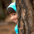 Girl peeks from tree. — Stock Photo #4890941