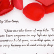 Stock Photo: Rose petals and love letter.