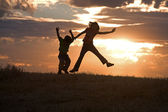 Kids jumping at sunset. — Stock Photo