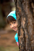 Girl peeks from tree. — Stock Photo