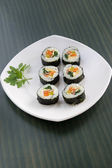 Six pieces of sushi and a parsley leaf. — Stock Photo