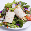 Tortilla wrap on top of salad. — Stock Photo