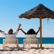 Couple sitting in sun chairs — Stockfoto
